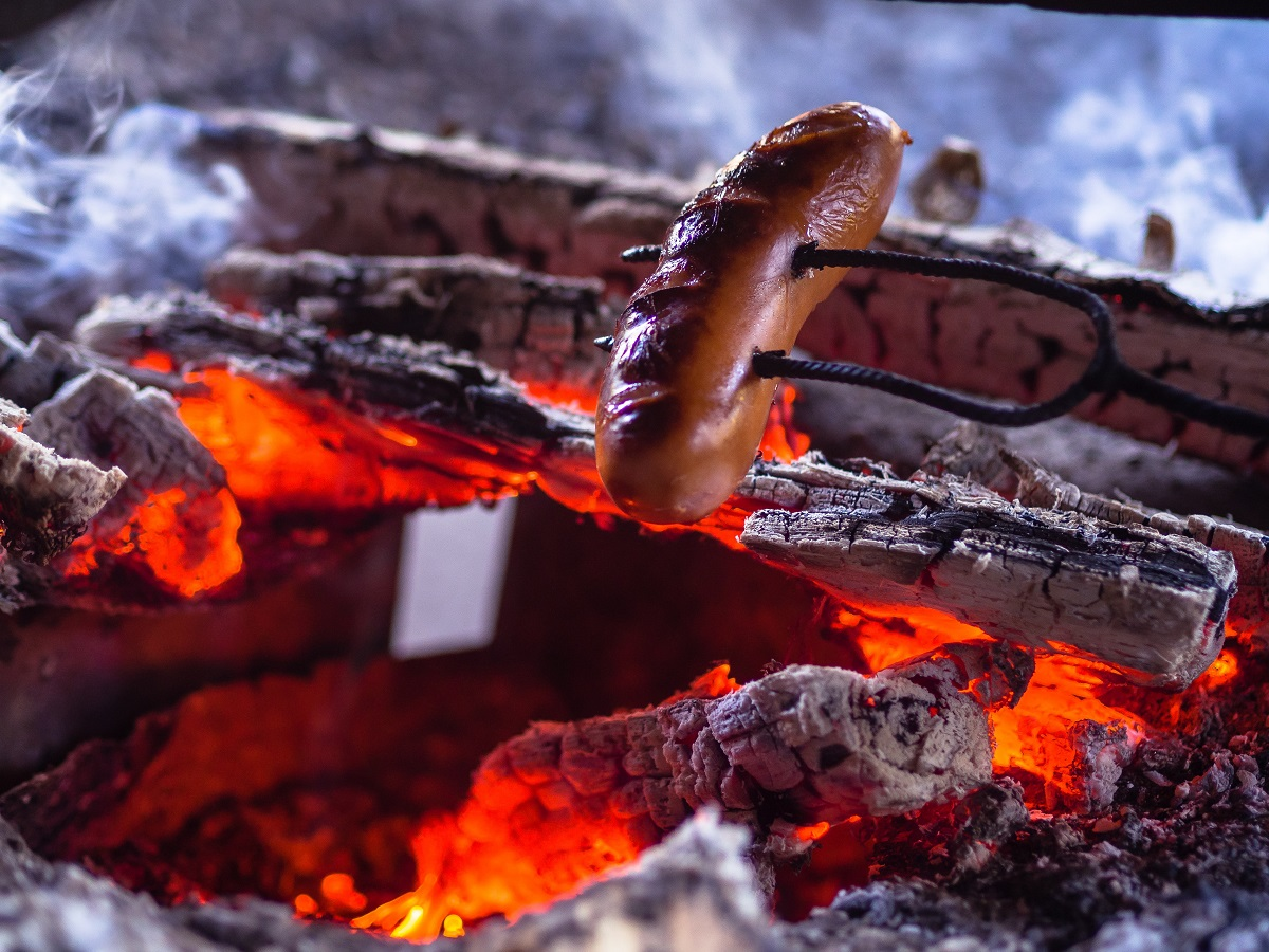 Gourmet artisan sausages on a camp fire